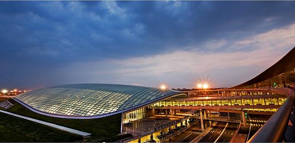 """记者最近在北京新机场施工区现场看到,航站楼主体结构已经露出地面,工程现场塔吊林立,航站区各项目正按计划有序实施。新机场航站楼为何要采用""""凤凰开屏""""的造型?旅客到新机场乘车是否方便?随着新机场容颜初绽,这些疑惑都得到了解答。 机场快线直达市内,到天津大约1小时 北京新机场位于北京的最南端,处于京津冀核心地带。据北京新机场建设指挥部新闻发言人朱文欣介绍,新机场距离天安门的直线距离为46公里,旅客到新机场的时间成本和经济成本可能较首都机场要高一些。因此新机场在建设之初就着力完善交通体系"""